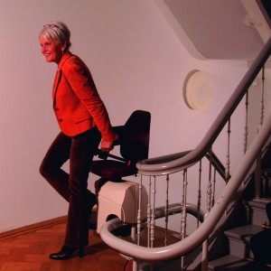 A lady about to sit on a stairlift