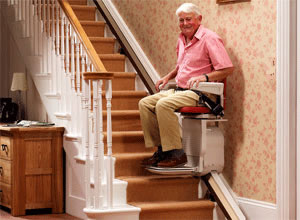 A man going up the stairs on a stairlift